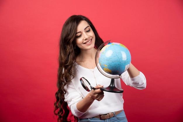 Gelukkige vrouw kijken naar globe op rode achtergrond. hoge kwaliteit foto