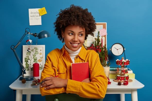 Gelukkige vrouw kijkt peinzend opzij, glimlacht breed, houdt een rood zakboekje en een potlood vast voor het schrijven van notities