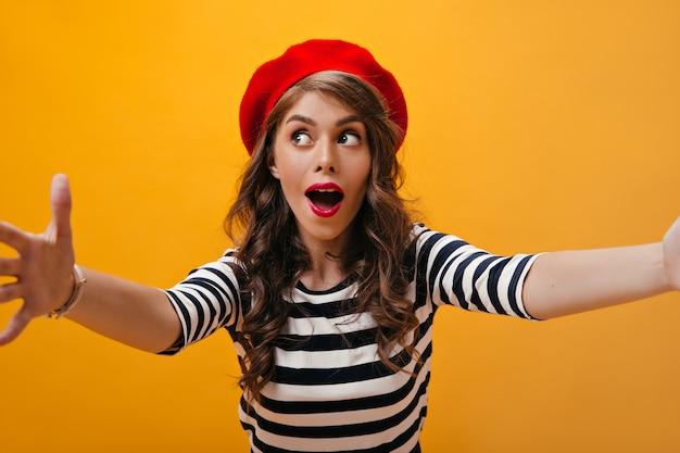 Gelukkige vrouw kijkt verbaasd en neemt selfie. charmante dame met blauwe ogen in rode baret en stijlvolle truien die zich voordeed op een oranje achtergrond.