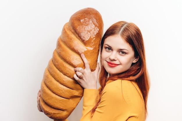 Gelukkige vrouw knuffelen brood meel product lichte achtergrond bijgesneden weergave