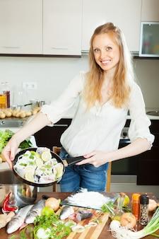 Gelukkige vrouw koken vis met citroen