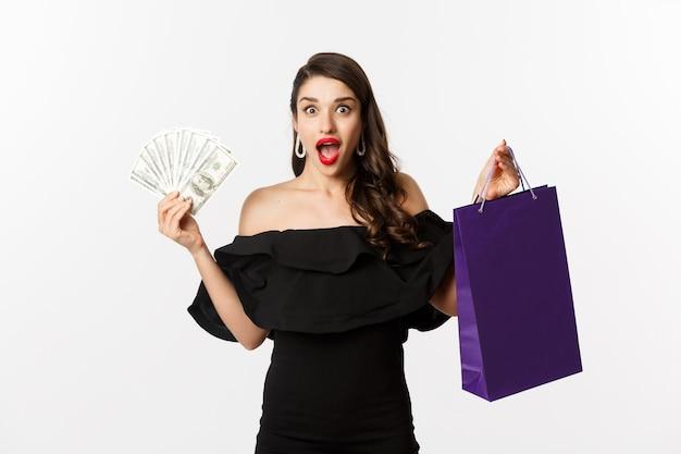 Gelukkige vrouw koper met boodschappentas en geld, staande in zwarte jurk op witte achtergrond. ruimte kopiëren