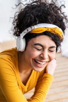 Gelukkige vrouw lachen en luisteren naar muziek op de koptelefoon