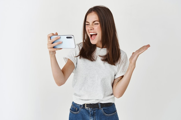 Gelukkige vrouw lacht en kijkt naar het smartphonescherm, kijkt naar grappige video's, staat over een witte muur