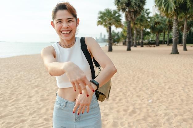 Gelukkige vrouw lacht en loopt op het strand