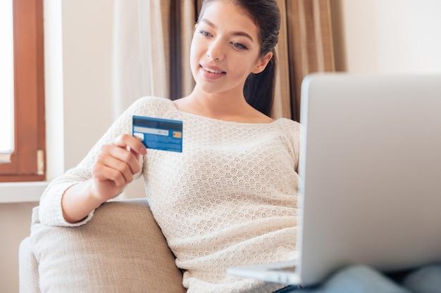 Gelukkige vrouw liggend op de bank met laptopcomputer en creditcard thuis