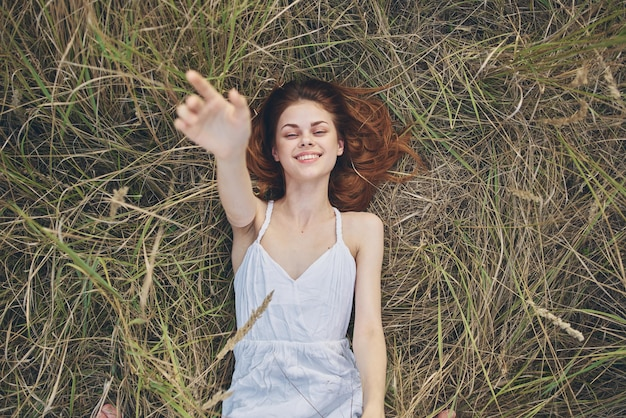 Gelukkige vrouw ligt op droog gras en gebaren met haar handen witte jurk.