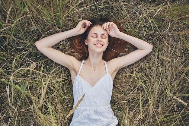 Gelukkige vrouw ligt op droog gras en gebaren met haar handen witte jurk