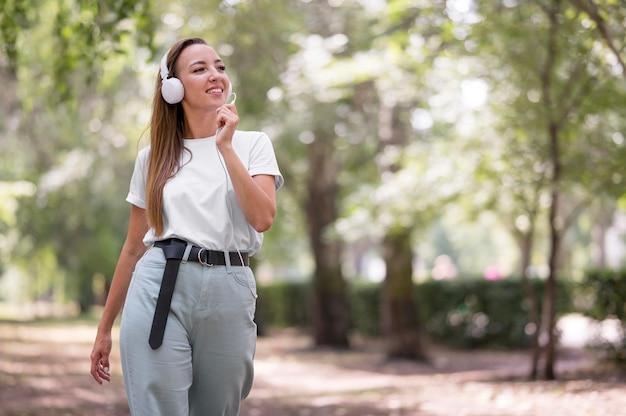 Gelukkige vrouw luisteren naar muziek via haar koptelefoon met kopie ruimte