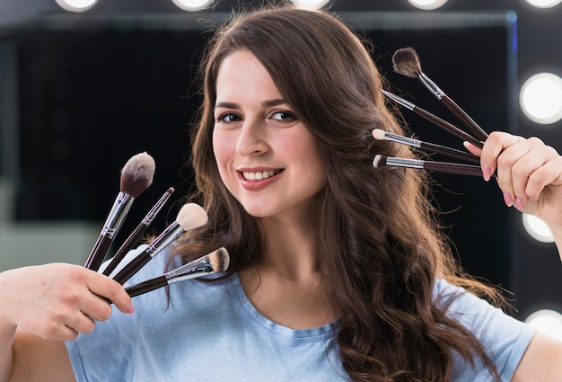 Gelukkige vrouw make-up artiest met penselen