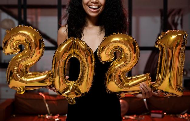 Gelukkige vrouw met 2021 ballonnen op feestje