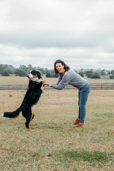 Gelukkige vrouw met actieve hond die buiten speelt vrolijke eigenaar en grote berner sennenhond hebben plezier op het veld tegen het dorpslandschap wandelen met huisdier