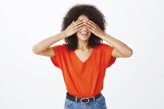 Gelukkige vrouw met afro kapsel poseren in de studio