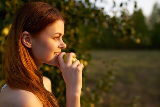 Gelukkige vrouw met appels in haar handen in de natuur groen gras bomen zomerzon