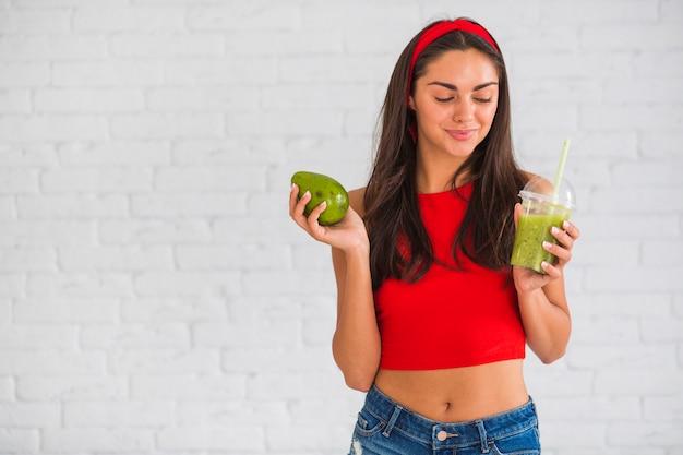 Gelukkige vrouw met avocado smoothies in plastic beker