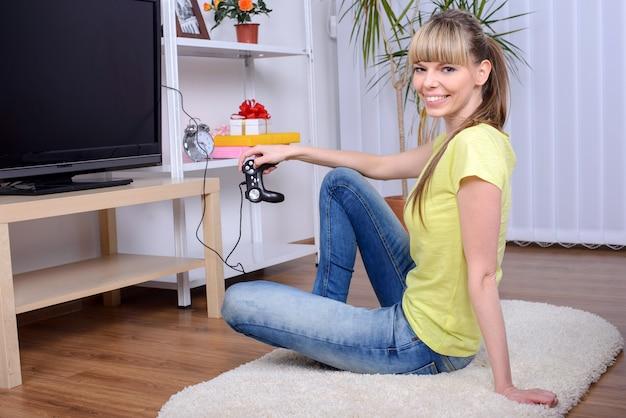 Gelukkige vrouw met bedieningshendel het spelen videospelletjes thuis.