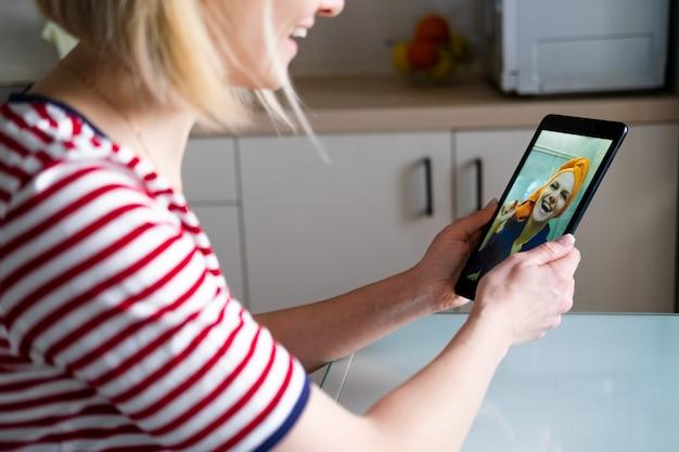 Gelukkige vrouw met behulp van digitale tablet voor video-oproep vrienden en ouders, lachend meisje zit thuis keuken plezier begroeting online door computer webcam maken videocall