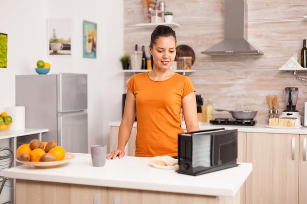 Gelukkige vrouw met behulp van elektrische broodrooster in de ochtend vrouw roosteren sneetjes brood op elektrische broodrooster