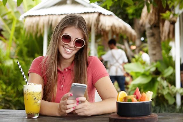 Gelukkige vrouw met behulp van gratis wi-fi op haar mobiele telefoon, scherm kijken met vrolijke flirtende glimlach