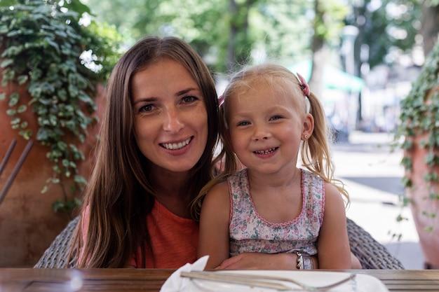 Gelukkige vrouw met blond meisje achter de tafel van een cafetaria.