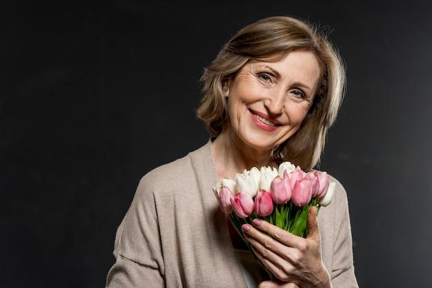 Gelukkige vrouw met boeket bloemen
