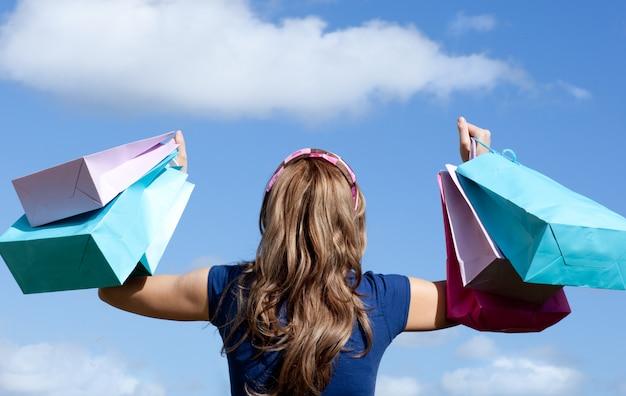 Gelukkige vrouw met boodschappentassen buiten
