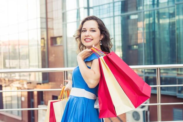 Gelukkige vrouw met boodschappentassen die tijdens het winkelen genieten van. consumentisme, winkelen, levensstijlconcept