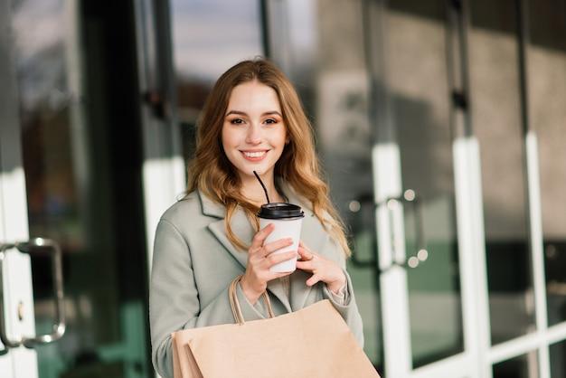 Gelukkige vrouw met boodschappentassen die van winkelen genieten. consumentisme, levensstijlconcept