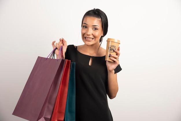 Gelukkige vrouw met boodschappentassen en koffie poseren op witte muur.