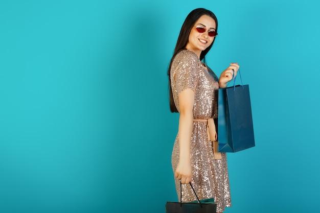 Gelukkige vrouw met boodschappentassen en lachend naar de camera.