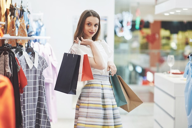 Gelukkige vrouw met boodschappentassen gaat naar de winkel. de favoriete bezigheid voor alle vrouwen, levensstijlconcept.