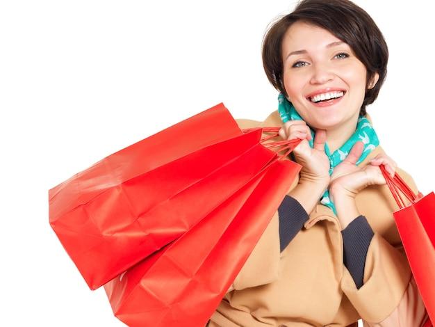 Gelukkige vrouw met boodschappentassen in beige herfst jas met groene sjaal geïsoleerd op wit