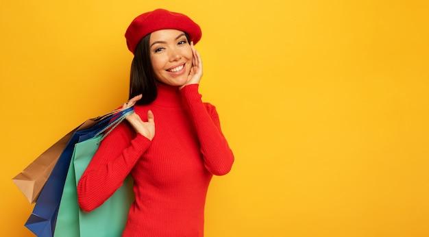 Gelukkige vrouw met boodschappentassen in de hand. gele bakground