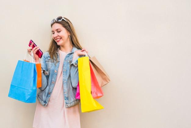 Gelukkige vrouw met boodschappentassen met behulp van smartphone