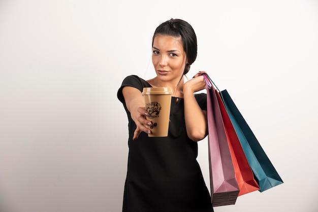 Gelukkige vrouw met boodschappentassen met kopje koffie naar de camera.