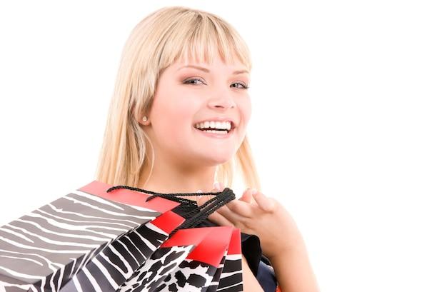 Gelukkige vrouw met boodschappentassen over wit
