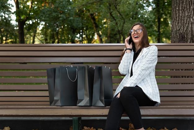 Gelukkige vrouw met boodschappentassen praten over de telefoon en lachen. mooie jonge vrouw rust in het park.