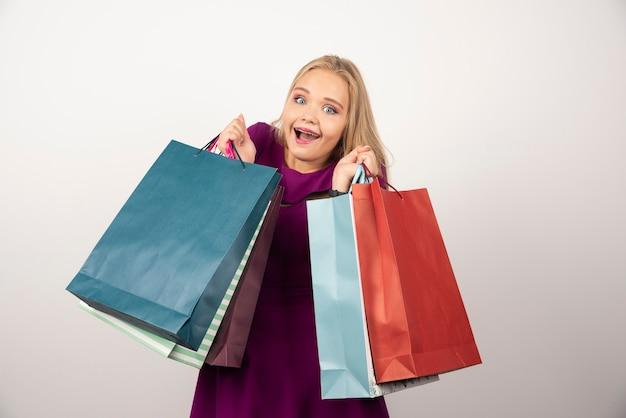 Gelukkige vrouw met boodschappentassen.