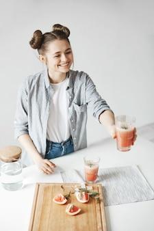 Gelukkige vrouw met broodjes glimlachend uitrekkende glas met grapefruit detox smoothie aan iemand. witte muur achtergrond. gezonde voeding.