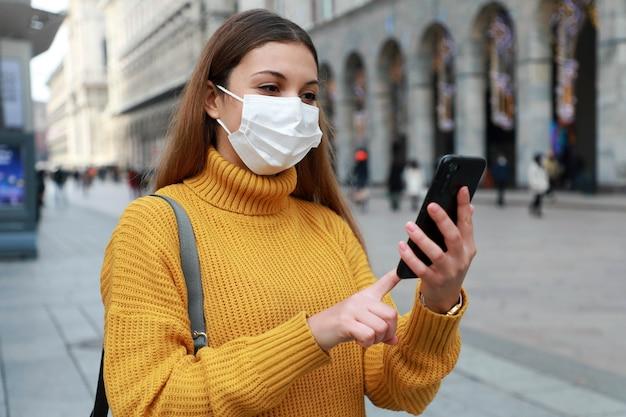 Gelukkige vrouw met chirurgisch masker online kopen met smartphone in de straat