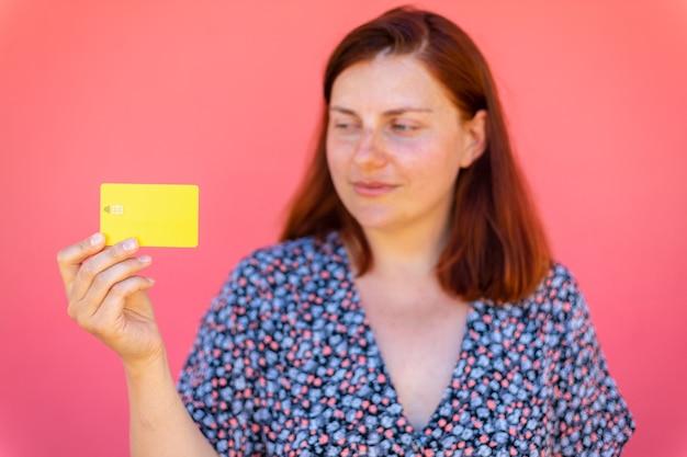 Gelukkige vrouw met creditcard in handen, staat in de buurt van een roze muur in de straat