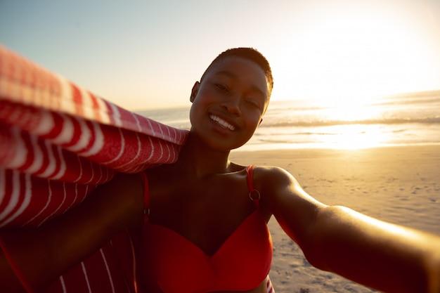 Gelukkige vrouw met deken die zich op het strand bevindt