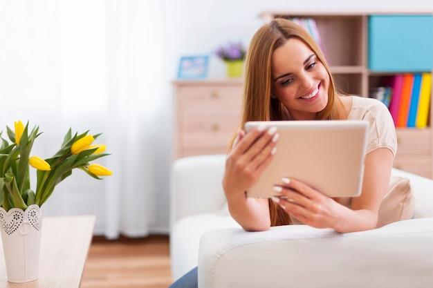 Gelukkige vrouw met digitale tablet thuis