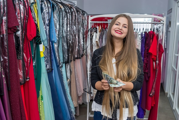Gelukkige vrouw met dollars in kledingwinkel