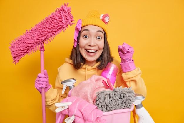 Gelukkige vrouw met donker haar balt vuisten voelt zich blij dat ze effectieve wasmiddelen en waspoeder gebruikt voor het reinigen van stof in de kamer die laudry doet, houdt dweil geïsoleerd over gele muur