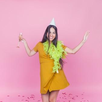 Gelukkige vrouw met drank die op roze achtergrond danst