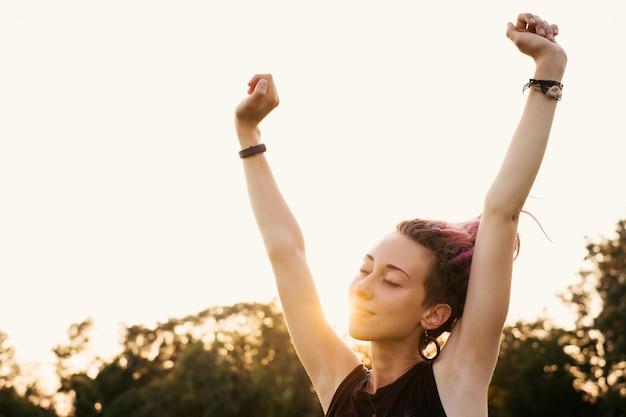 Gelukkige vrouw met dreadlocks die zich uitstrekken en frisse lucht inademen bij zonsondergang. meisje vol energie