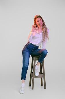 Gelukkige vrouw met dreadlocks zit op stoel onder kleurrijke lichten