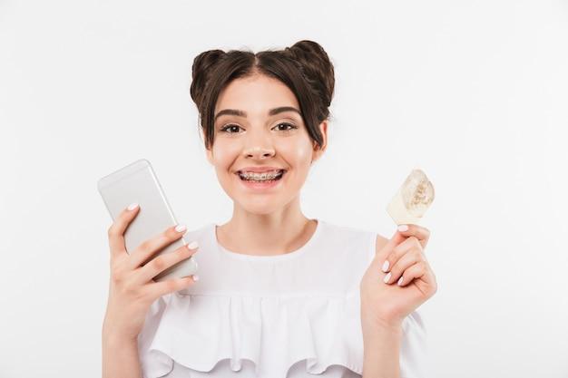 Gelukkige vrouw met dubbele broodjes kapsel en beugels die naar je kijken terwijl ze smartphone en creditcard in beide handen houdt, geïsoleerd op een witte muur