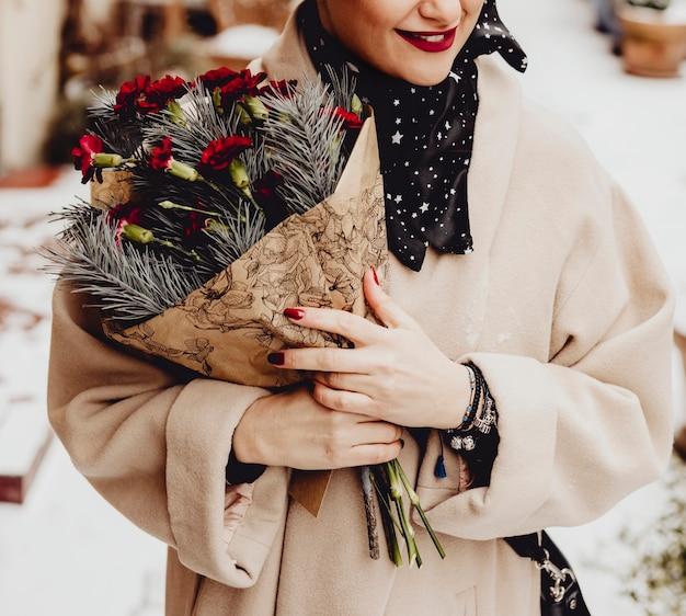 Gelukkige vrouw met een boeket bloemen in de winter